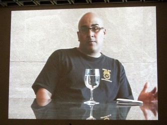 A screen shows a person in a black tshirt talking to camera