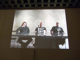 A screen shows three people looking seriously at camera