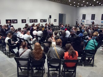 A audience sat on black wooden chairs in a large gallery watches Sean Meehan
