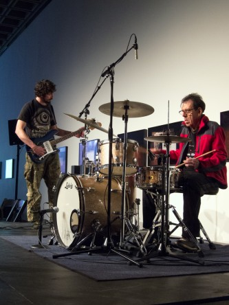 Tom Bruno in a red sweater and glasses plays drums whilst Matt plays bass