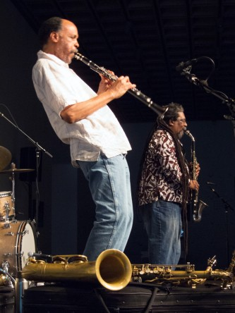 Daniel Carter leans back as he plays a clarinet, Sabir Mateen plays behind him