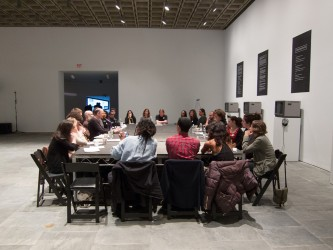 A large group of people sit around a large table in a gallery