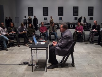 George Lewis sits at a small desk with laptop in the middle of a circle of folk