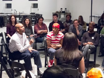 Frank Roberts speaks into a microphone as participants sit in a circle