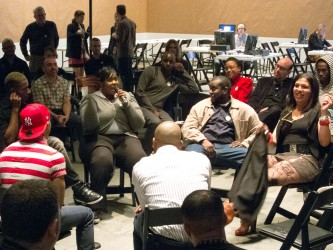 A participant talks into the mic whilst others sit in a circle