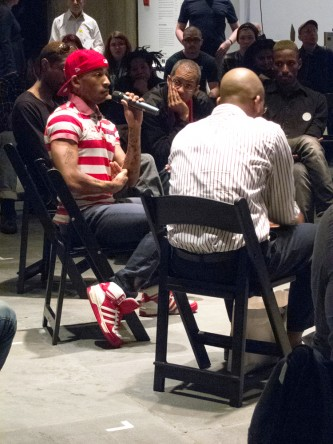 Pony Zion Garcon speaks into a microphone as participants sit in a circle