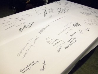 A table covered in white paper has been written on with marker pen
