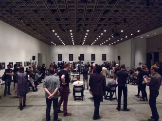 A large gallery is crowded with folk standing and sitting to hear a performance