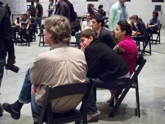 A group of people sit on black folding chairs listening to a performance
