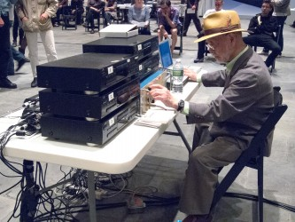 Yasanao Tone in a straw hat performs in front of stacks of equipment on a table