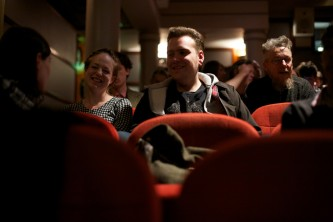 An audience sit and wait in red cinema seating