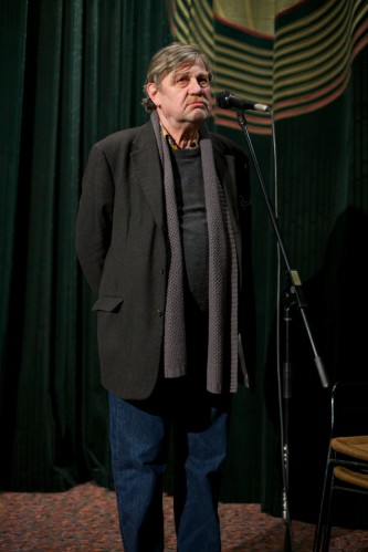 Harmut Bitomsky stands hand behind back in front of a cinema curtain
