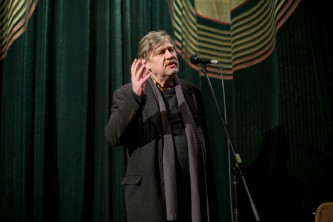 Harmut Bitomsky stands hand to face back in front of a cinema curtain