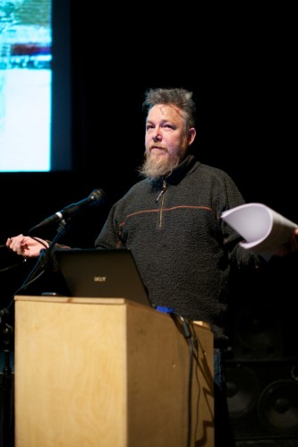 Graham Harwood stands at a lecture arms wide