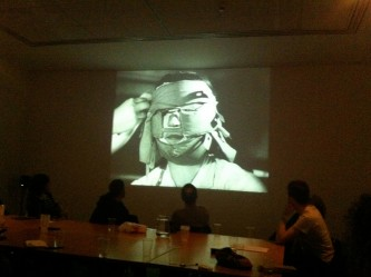 A shot of a screen showing a face swaddled in fabric