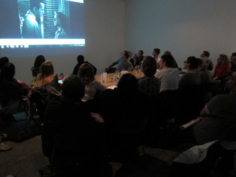 The audience around a large table with a screening on the wall
