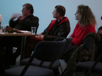 Hartmut Bitomsky gesticulates during a discussion with two audience members