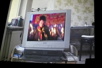 A shot of a screen showing Hito Steyrel film, showing her on a TV screen