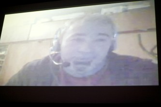 A fuzzy projected image of a Skype call with a member of Chto Delat