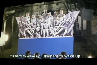 A shot of a screen of a film by Chto Delat with a large cutout sculpture is show