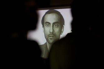 A screen shows a man looking straight ahead