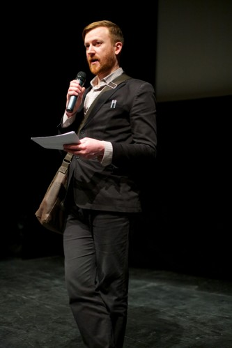 Barry Esson in a suit holds and mic during an introduction