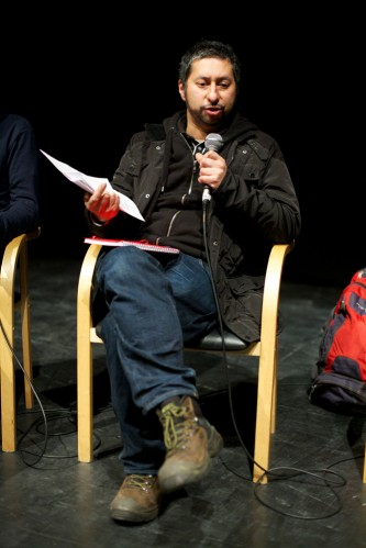 Sacha Kahir sits and holds paper and a mic during a discussion