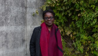 Denise wears a long read scarf and glasses