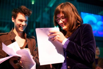 Amanda Monfroe and Iain Campbell smile as they look at a script
