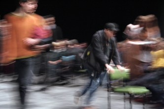 Dawn moves a green chair in a space with audience, the photo has blurred