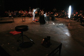 A long shot of Dawn Kasper in a performance space with working lights