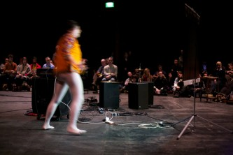 Dawn moves in a yellow jacket and bare legs in a space with sound equipment