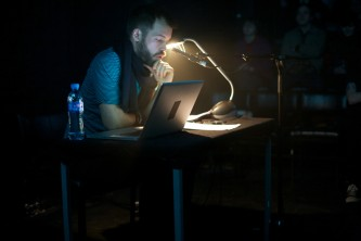 Evan Calder Williams behind a desk in dark foggy space illuminated by lamp