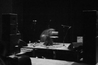 A spectral form performs on a stage, in a very dark room. A B&W picture