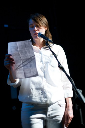 Malin Arnell in white clothes stands and reads from a paper