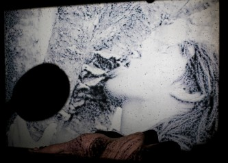 The back of naked figure is projected on with a black and white image