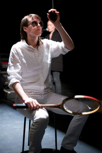 Malin Arnell in white and sunglasses holds a tennis racket and suspended ball