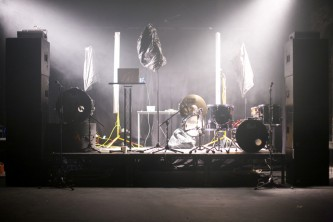 A stage set with vertical lights, fog, speakers and a mic covered with a bag