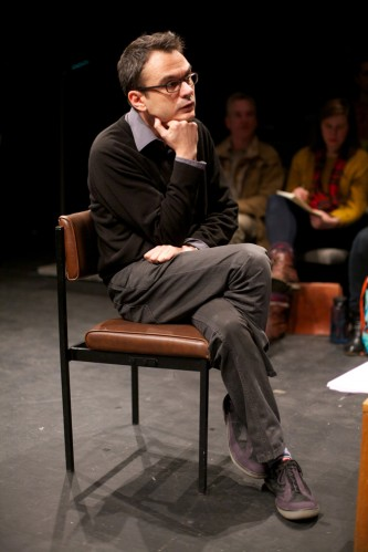 Ray Brassier, legs crossed with hand on chin, listens