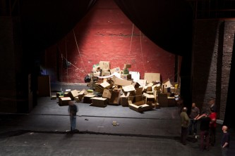 A huge pile of cardboard boxes on a stage in a theatre space