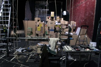 A huge pile of cardboard boxes on a stage in a theatre space, from backstage
