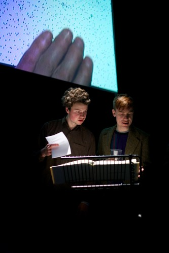 Two audience members look at a book on a stand as a screen with a hand is behind