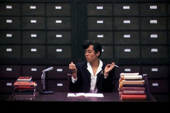 A shot of a screen showing an old office with a character in a suit at a desk