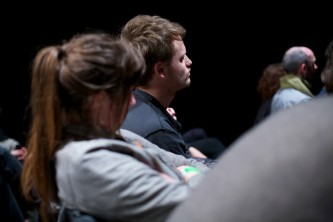 A member of the audience in profile asking a question