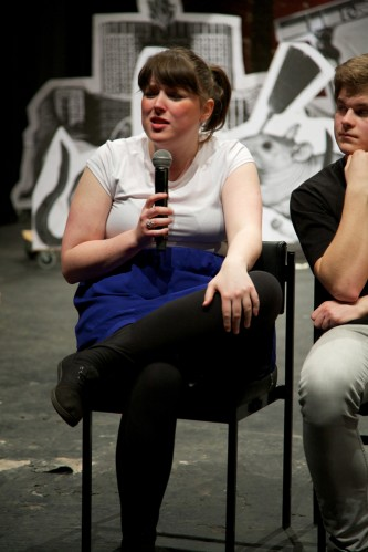 A cast member talks on a microphone whilst seated in front of the stage