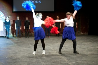 Two cheerleader type characters dance enthusiastically with pompoms