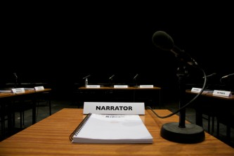 A square of empty desks set with microphone and scripts and character names