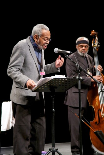Amiri Baraka reads poetry at a microphone and Henry Grimes plays a double bass