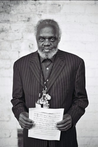 A portrait of Henry Grimes in a pin stripe suit in front of a white brick wall