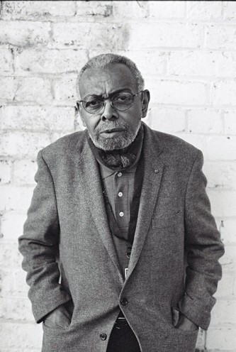 A portrait of Amiri Baraka in front of a brick wall he wears a quizzical smile